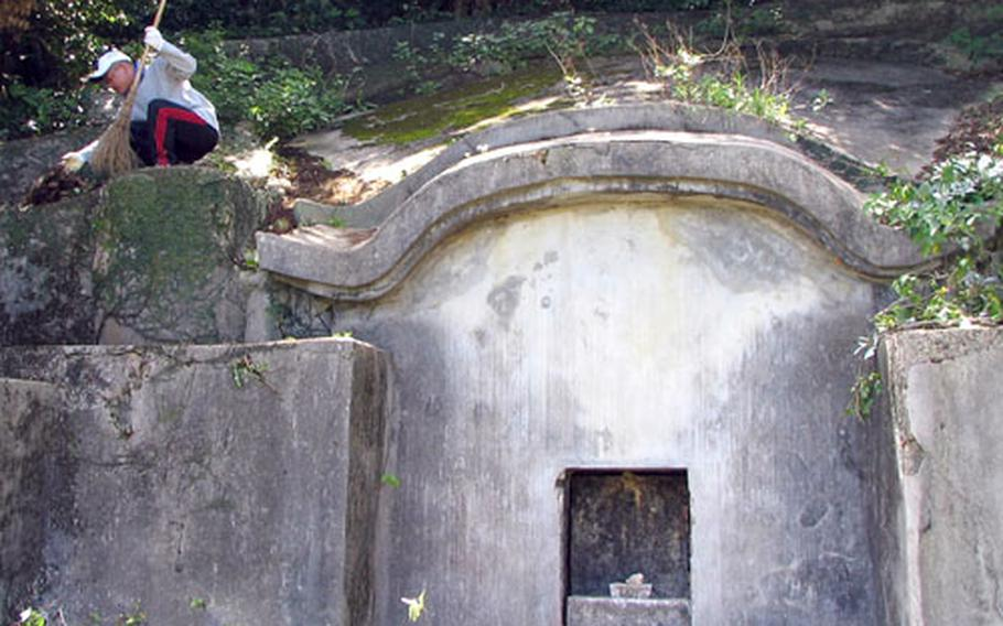 Isao Tsuha cleans brush from his family's centuries-old tomb on Okinawa in preparation for the annual shima festival, a time when families gather at the tombs of their ancestors for prayers, good food and a good time.