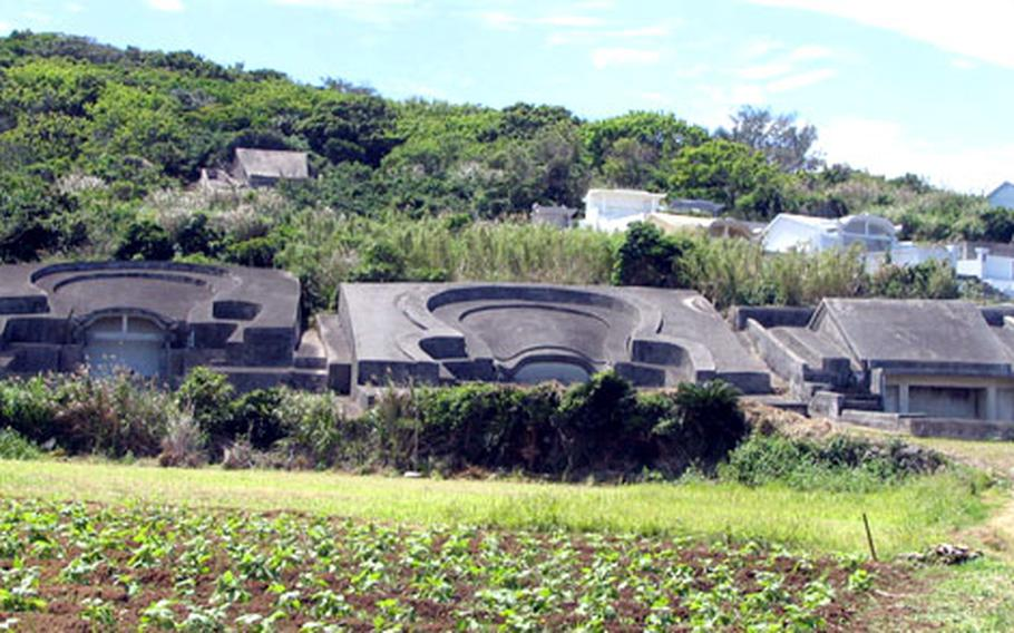 """Okinawa turtle back tombs and the more modern """"house"""" tombs dot a hillside in the Nagahama district of Yomitan. Adopted from China in the 16th century, Okinawans reinterpreted the meaning of the turtle shapes, believing the tombs represented a woman's womb."""