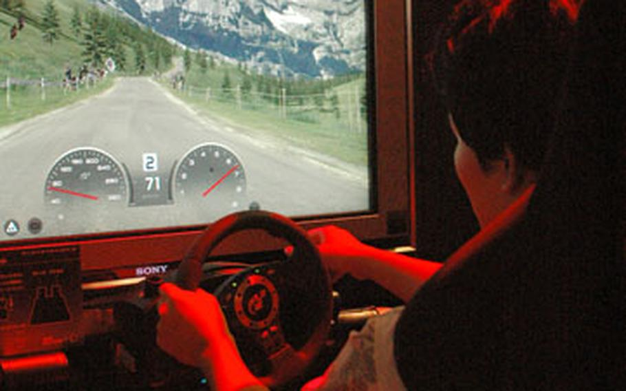 """A gamer tries his hand at """"Gran Turismo HD,"""" a racing game for the Sony Playstation 3."""