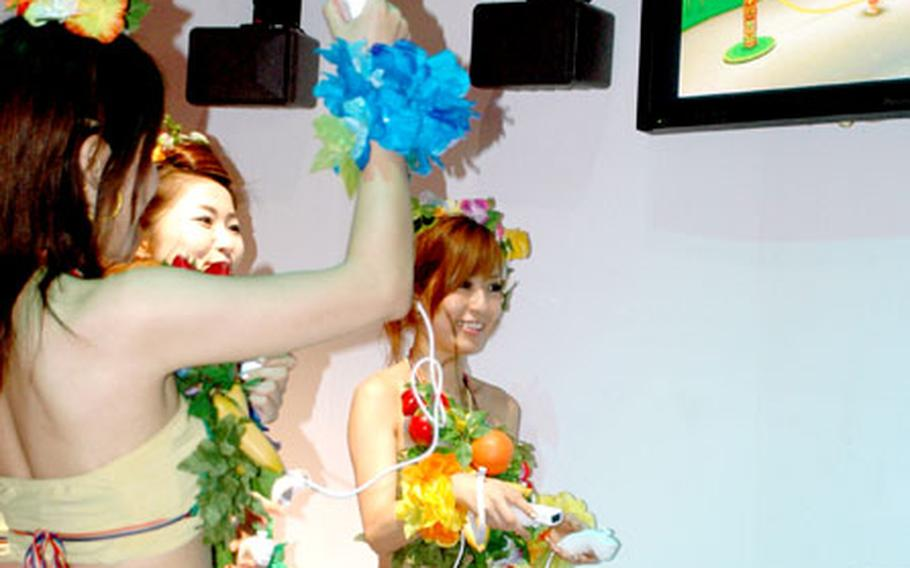 """Booth babes demonstrate how to play a jump rope mini-game on Sega's new """"Super Monkey Ball"""" for the Nintendo Wii."""