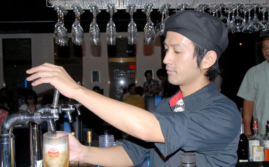 A bartender at Cure in Chatan, Okinawa, fills another beer order.