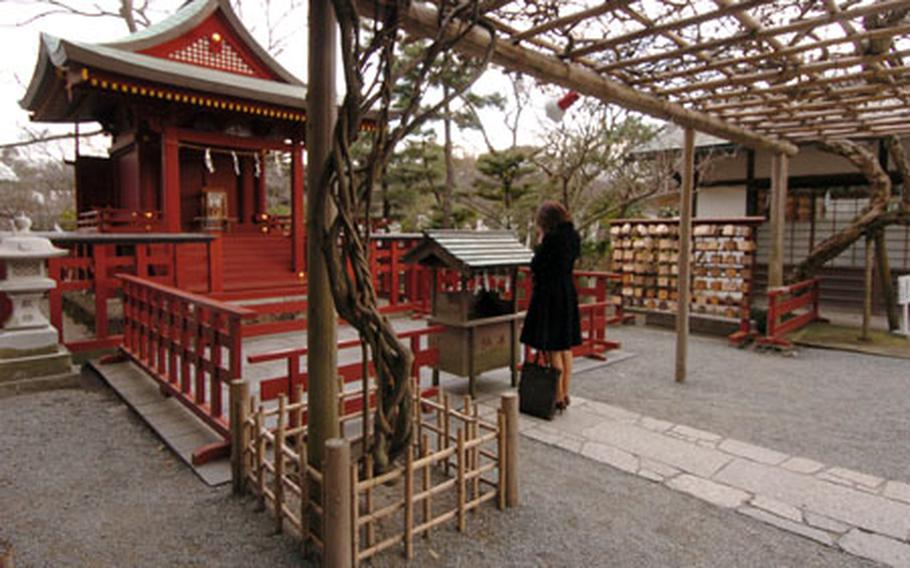 A Japanese woman pays respects by tossing money and praying at a Hachimangu shrine in Kamakura. The Hachimangu shrine is dedicated to the memory of samurai and has many events held at it each year. The main halls act also as a museum, and the ponds and parks are open to the public.