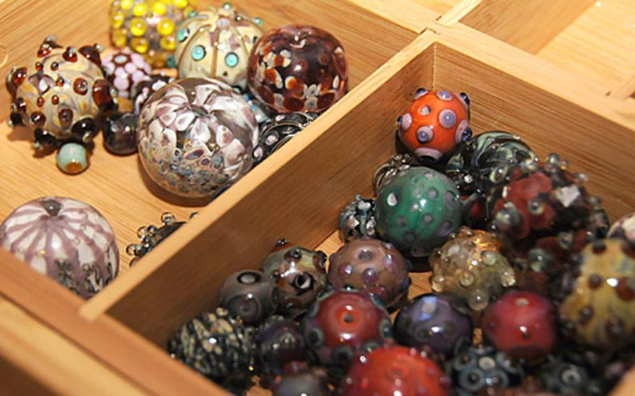 """""""Each bead is a work of art,"""" Julia Landecker says of the glass beads she makes in a workshop in her home. She finds it easier to just create numerous beads and then build jewelry from them, rather than try to create a set of beads for a specific peice of jewelry."""