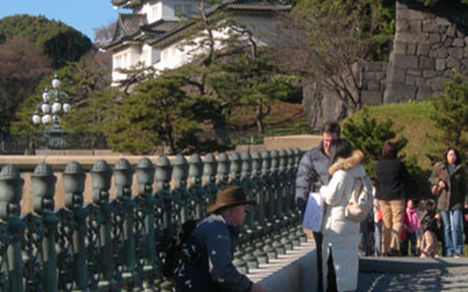 The Imperial Palace sits on a hill in the distance as a backdrop for visitors' photos of in Tokyo, Japan.
