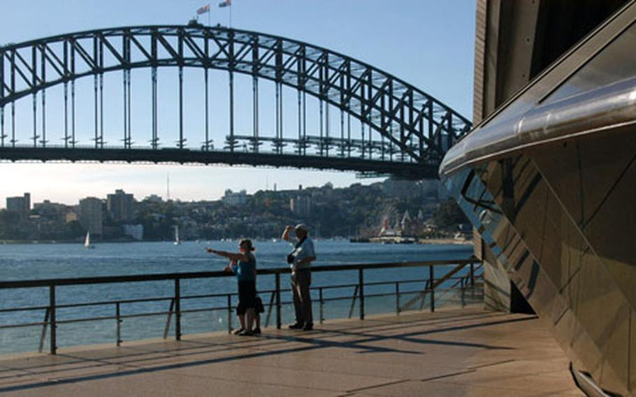 Standing near two of the city's landmarks — the Opera House, right, and harbour bridge — tourists point toward the downtown area.