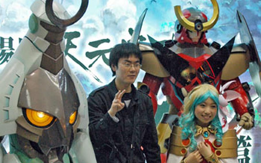 An anime fan poses for a picture with exhibitors dressed as anime characters at the Tokyo International Anime Fair.