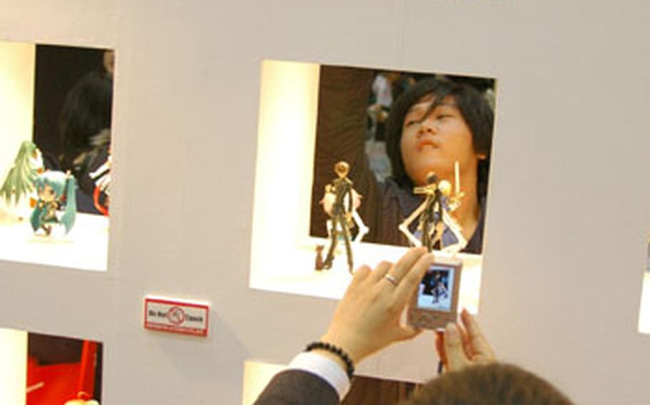Anime fans take pictures of figurines on display at the 2009 Tokyo International Anime Fair.