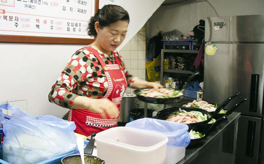 """At the Kim Neh Jeep restaurant, owner Kim Myong-ja readies pans of the house specialty, """"bu-tehchi-geh,"""" a spicy stew that came about during the hard days of the Korean War."""