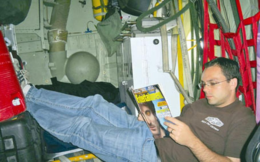 Tim Wightman relaxes with a magazine during a space-available flight aboard a C-130 bound for Naval Air Facility Atsugi, Japan.
