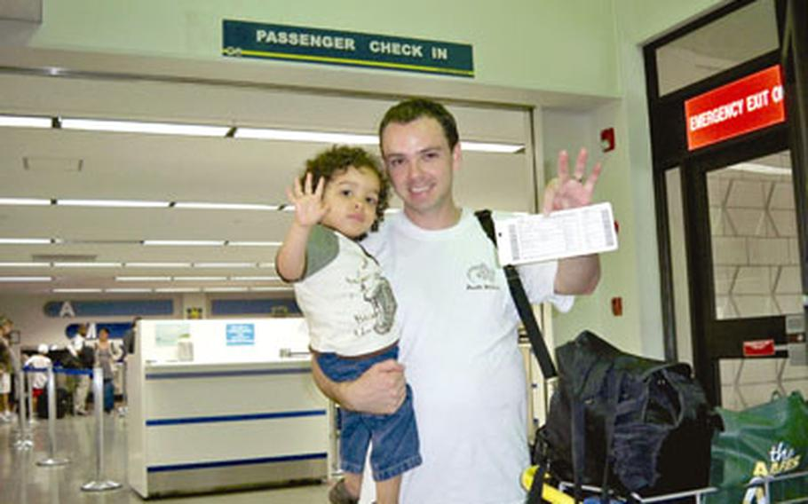 Tim Wightman holds up his son, Dallin, and three boarding passes for one of his family's Space-A flights.