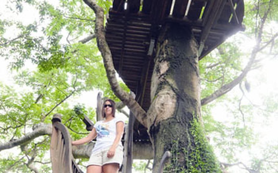 The author's wife, Lea, stands at the bottom of the main attraction of the Beach Rock Village: the tree house. It has a commanding view all the way to the ocean.