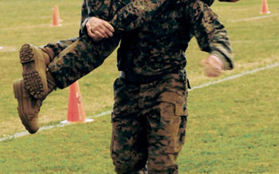Sgt. Jason Cortes carries Sgt. Michael Williams in the fireman's carry part of the maneuver-under-fire leg of the Corps' combat fitness test.