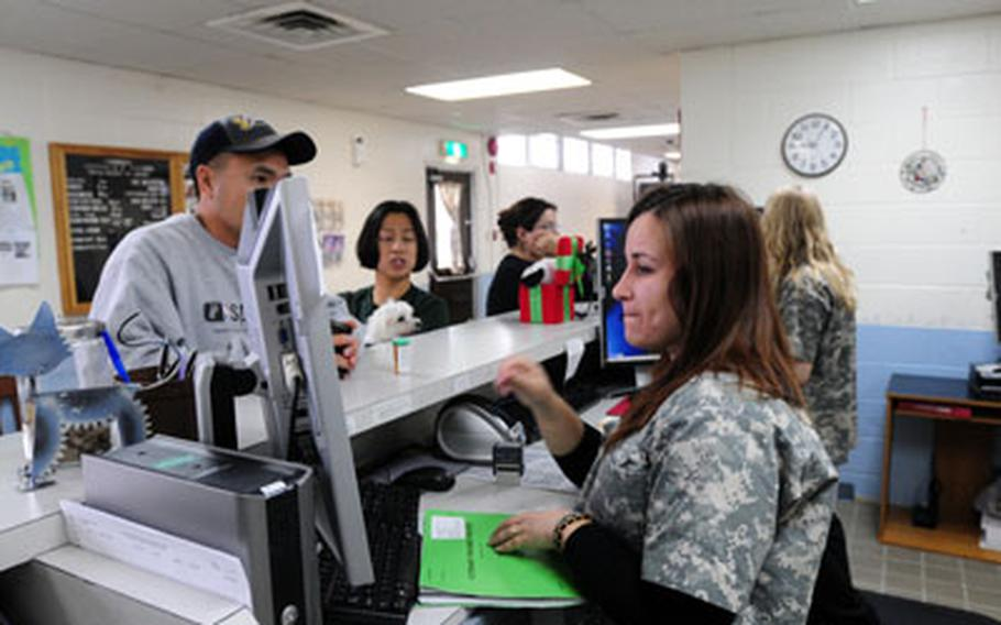 Jonelle Judge and Brittany Jungewaelter check in pet owners waiting to have their pets seen at Kadena's Veterinary Treatment Facility.