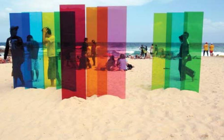 """Beachgoers enjoy the natural beauty in front of one of the many pieces in the Sculpture by the Sea Exhibit at Bondi Beach. The piece, created by Nicholas Elias and titled """"a symbolic inscription of the imaginary,"""" was one of the many spectacular pieces I viewed that day on the breathtaking Sydney shores."""