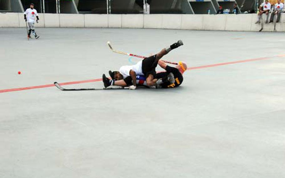 Players take a tumble during a recent CBHK (Canada Ball Hockey Korea) game in Seoul, South Korea. While fighting and bone-crunching checks are not allowed, the league does feature some pretty aggressive play and occasional injuries.
