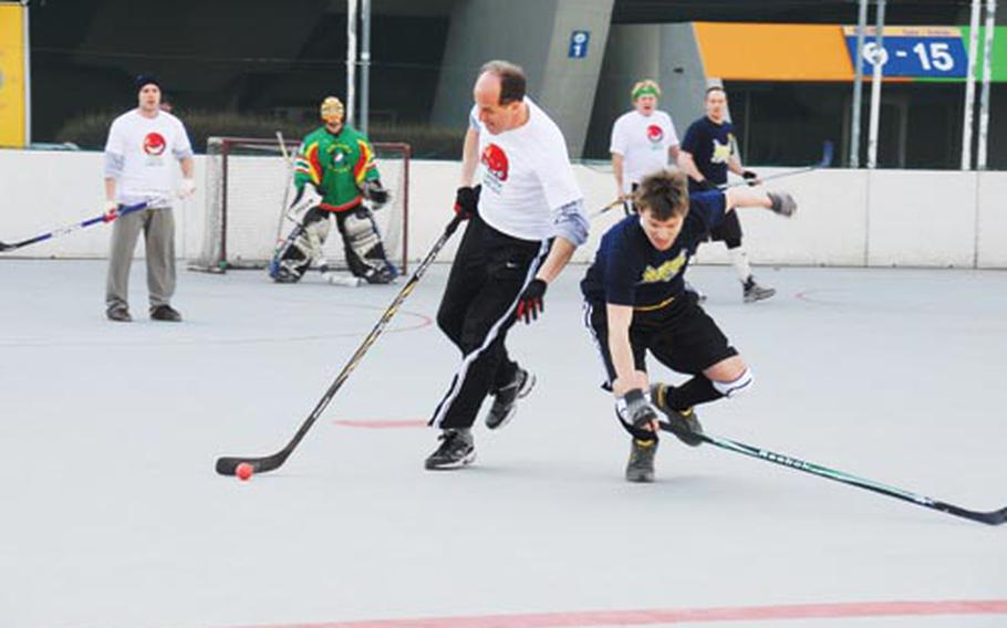 Stars and Stripes reporter Jon Rabiroff, center in white, stick-handles past a falling defender during a recent CBHK game. Rabiroff, 50, is apparently the oldest player in the league.
