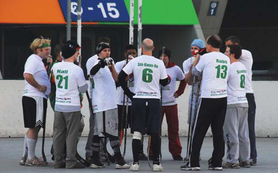 """Members of the Around Seoul Savages talk strategy during a break between recent CBHK games. Many of the league's 120 players sport nicknames on their team shirts, including """"Rabs,"""" a college nickname of Stars and Stripes reporter Jon Rabiroff."""