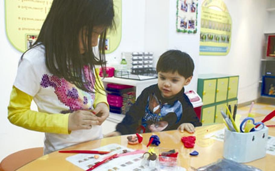 Natalya and Diego Jimenez create characters using clay from the Character Hall at the Seoul Animation Center.