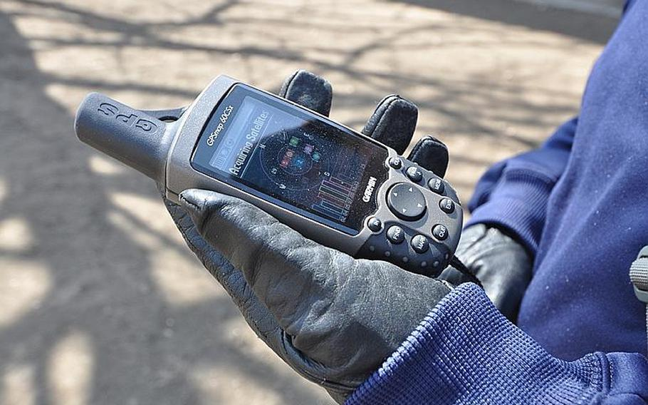 Tech. Sgt. Robert Slagle checks the satellite strength on his hand-held GPS device during a demonstration in Misawa City in April. Slagle is president of the Misawa Geocachers Organization at Misawa Air Base, Japan.