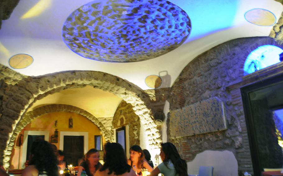 Customers dine under the tufa arches of the former cloister's arcade at the trendy bar and restaurant Il Chjostro in Aversa, Italy, near the Navy base in Gricignano.