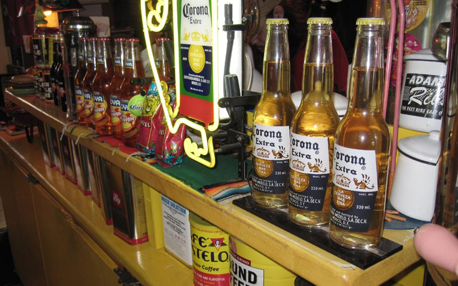 Bottles of Corona and various other imported beers are displayed on the shelves at Okinawa's Sea Side Jet City Burgers, lending to the feeling that you have walked into a diner in America.