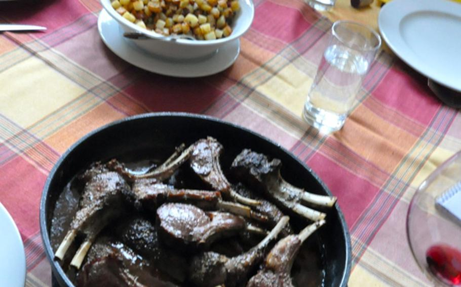 A pan full of tender lamb chops, sauteed, with a plum sauce on the side, is served with two family-style bowls of vegetables, home fried potatoes and  sliced steamed carrots in a dill sauce.