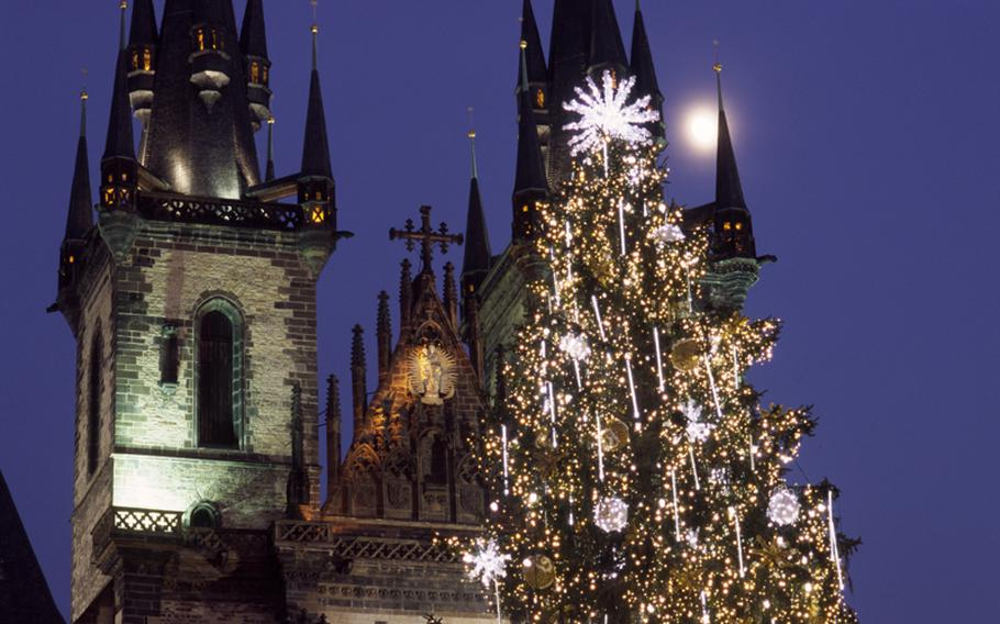 White lights and candles on one of the large Christmas trees at Prague's main Christmas market stands out against the Gothic spires of Tyn Church.