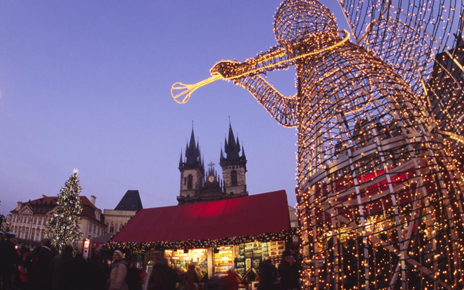 An angel made of wire and lights heralds another holiday season at the main Christmas market in Prague, Czech Republic. In the background, the spires of the 14th-century Tyn Church tower over market booths.