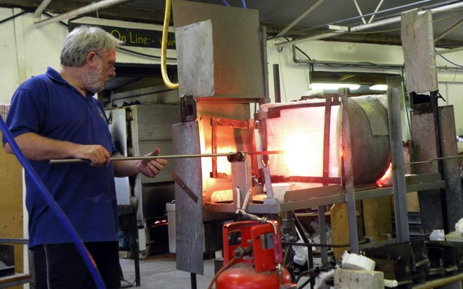 Glassmaker John Wainwright places a rod with molten glass attached into a furnace.