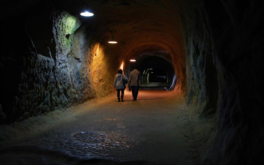 Visitors to the Yoshimi Hyakuana cliffs explore the long, eerie passageways of caves that used to be part of a munitions factory.