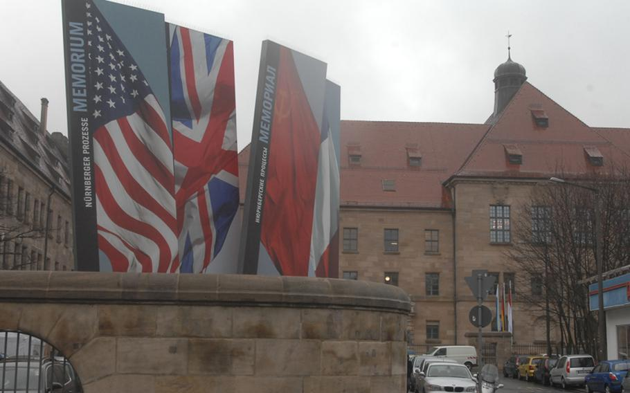 A display for Memorium Nuremberg Trials depicts the flags of the victorious Allied Powers in World War II  -- the United States, Britain, the Soviet Union and France -- who tried the captured Nazi leaders for war crimes and crimes against humanity. The building in the background is the Nuremberg Palace of Justice where the suspects were tried.