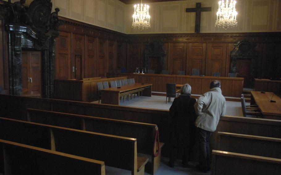 A couple gazes at Court Room 600, the room where the surviving leaders of the Nazi regime were tried for their crimes after World War II. It is in the  Nuremberg Palace of Justice and is still used for criminal trials.