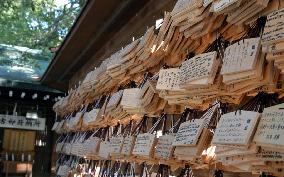 Wooden plaques called ema are hung on rails at Meiji Jingu in Tokyo. These are a way to make wishes or prayers. You write them down and hang them at shrines to be read by deities.
