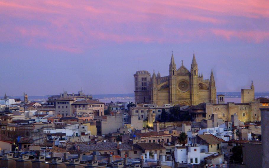 The Cathedral of Santa Maria of Palma rises from Majorca into the brightly colored clouds at sunset.