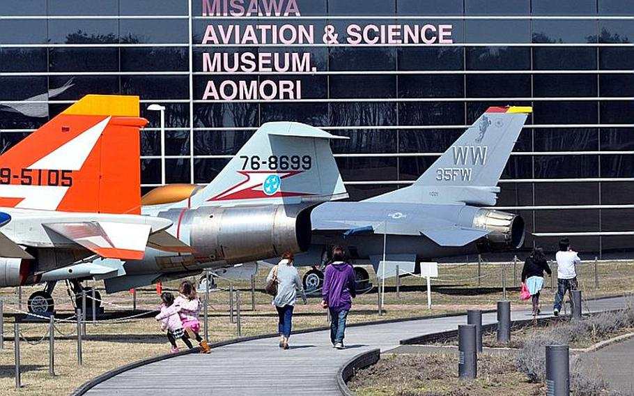 Visitors walk past a line of static display aircraft toward the entrance of the Misawa Aviation and Science Museum Aomori on April 10.