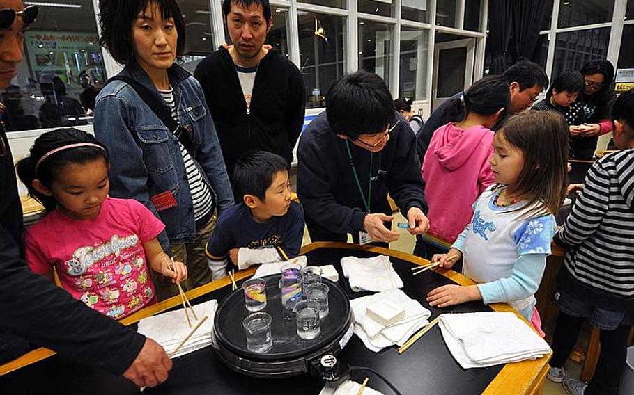 Children make fossil keychains with soft rubber and a mold during a class at the Misawa Aviation and Science Museum Aomori on April 10. While the instruction is primarily in Japanese, the projects are usually easy enough for foreigners to enjoy.