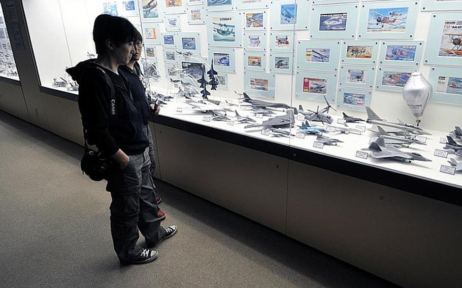 Visitors check out some of the hundreds of airplane models that line a long hallway on the second floor of the museum.