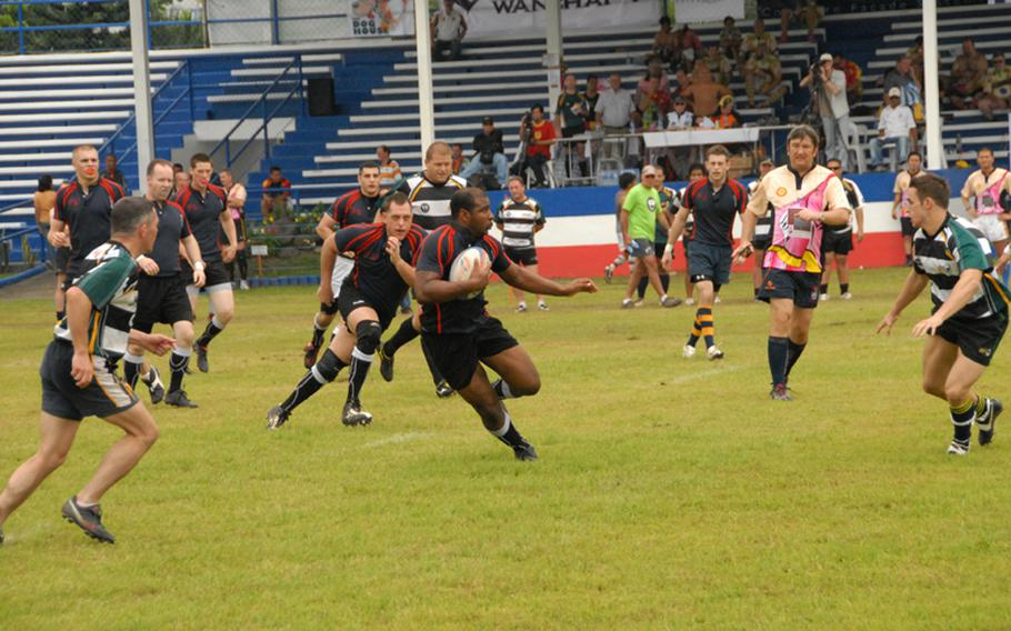Petty Officer 2nd Class Rayshawn Coleman runs with the ball during a rugby match last September while in port in the Philippines.