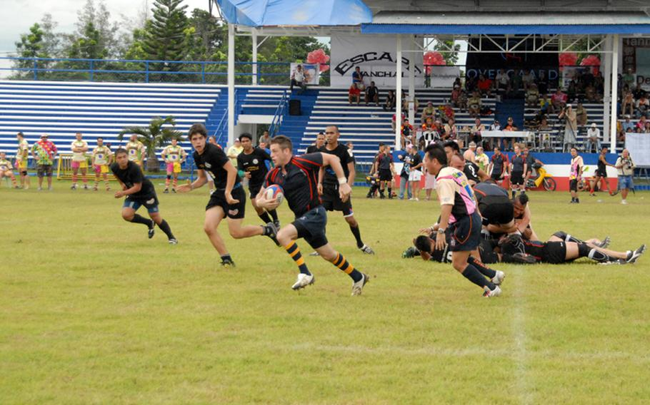 Petty Officer 3rd Class Mike Kaltsunas sprints away from defenders during a rugby match last September while in port in the Philippines.