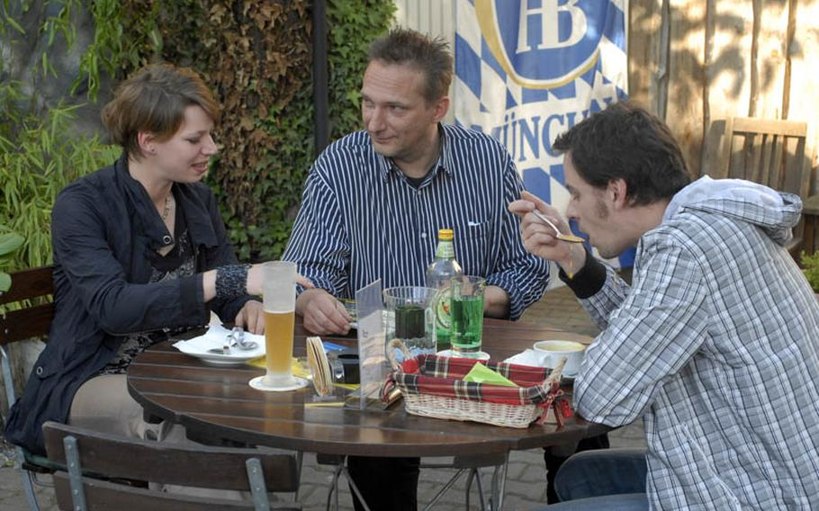 Oliver Wasserfuhr, center, manager of the Gasthaus Zum Engel, takes time out to talk to guests in the restaurant's spacious outdoor beer garden.