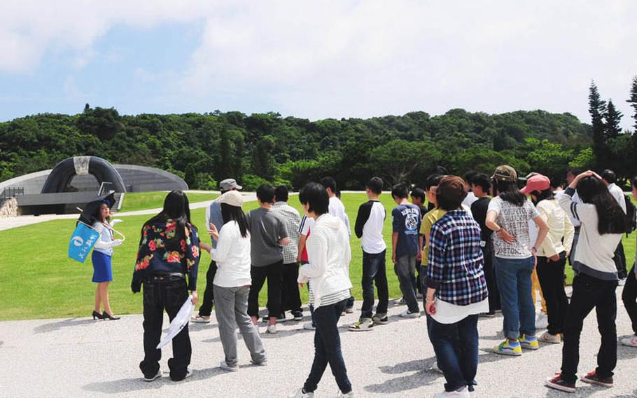 A group of students listens to a tour guide talk about the Hill of Peace. The large structure is meant to represent a cave where many Okinawans hid during the Battle of Okinawa.