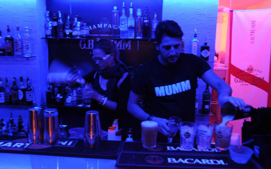 Bartenders mix up a variety of cocktails at G.H. Mumm in the port area of Pozzuoli, a suburb of Naples. The pub is down a narrow alley instead of in the middle of a piazza, one of the pub&'s alluring features.