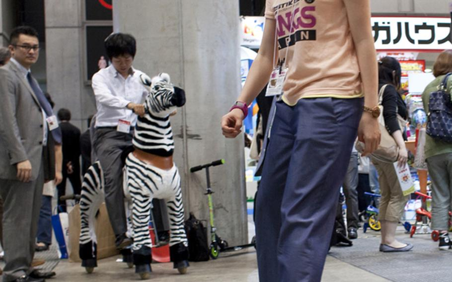 A worker with Rangs Japan rides a Ripstik, a skateboard-like toy with rollerblade wheels at the toy show on June 16.