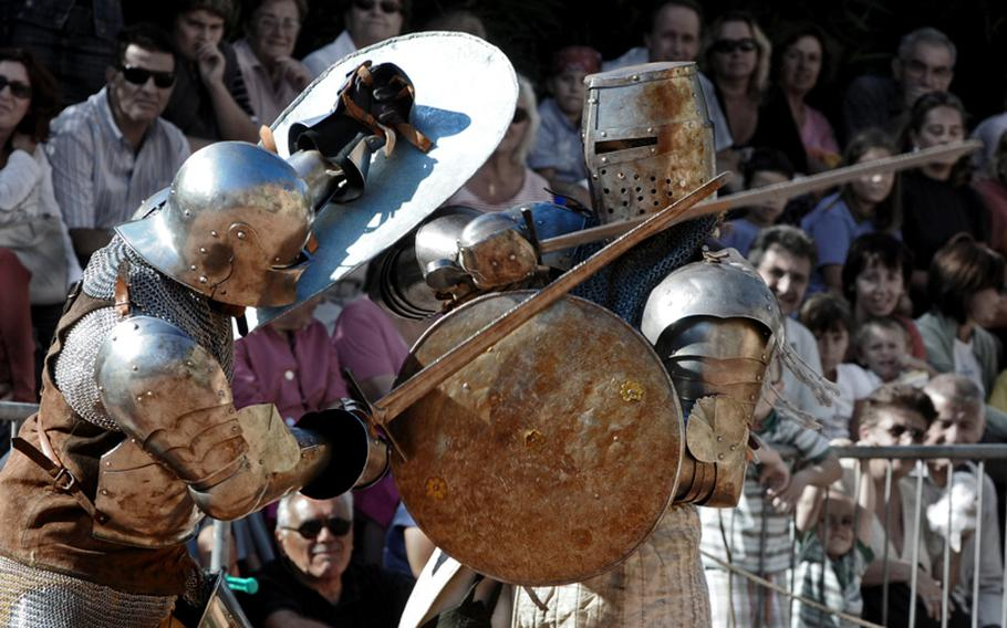 Knights wielding swords and shields clash during the fest as a crowd gathers to watch.