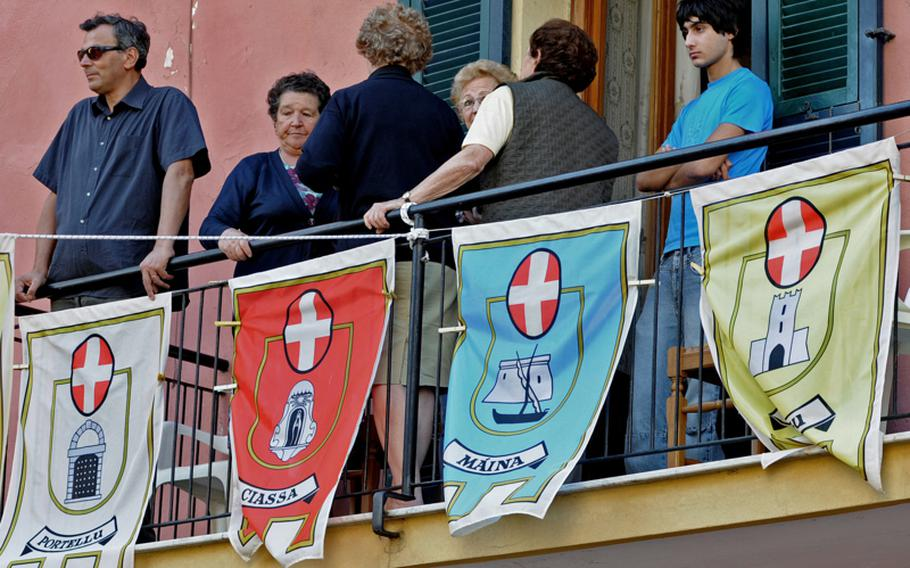 Flags of the old districts of Noli decorate a modern-day balcony during the town's medieval festival.