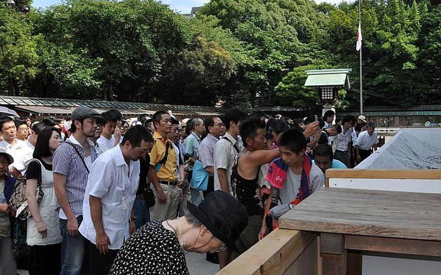 People gather at the shrine to pray and make their donations. The line to pray at the shrine extended all the way across the pavilion.