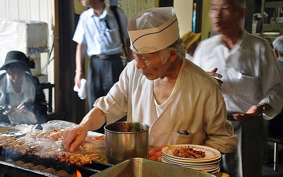 A man cooks yakitori at Yasukuni Shrine. The August 15 event gathered hundreds of people to pray and make donations.