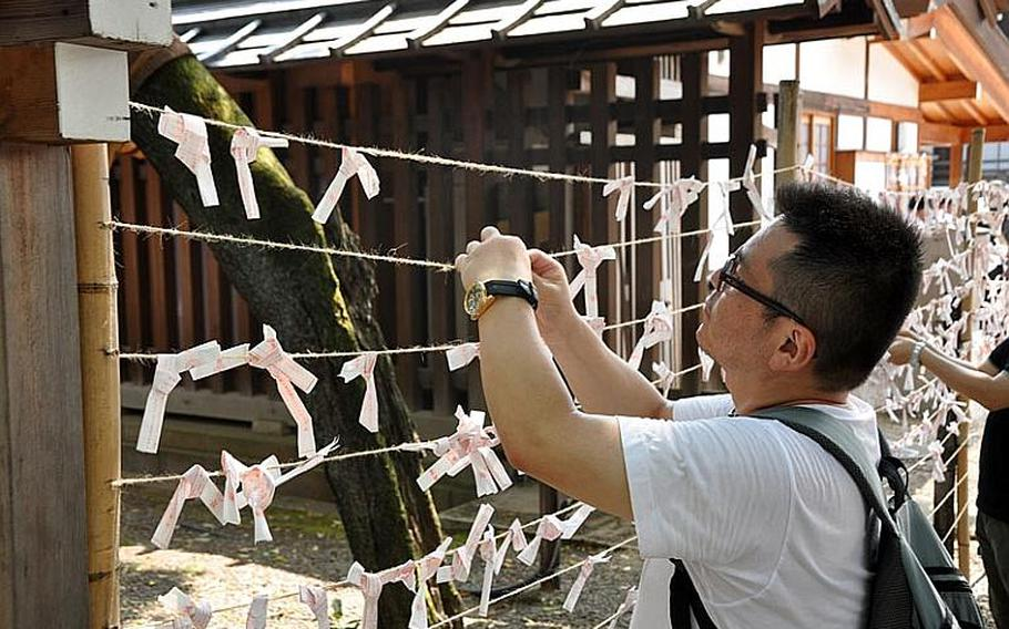 A man ties an omikuji around some twine. Omikuji means fortune from the gods. Worshipers tie these as a prayer to either improve the fate the fortune prophesies or ensure it depending on whether the fortune is good or bad.