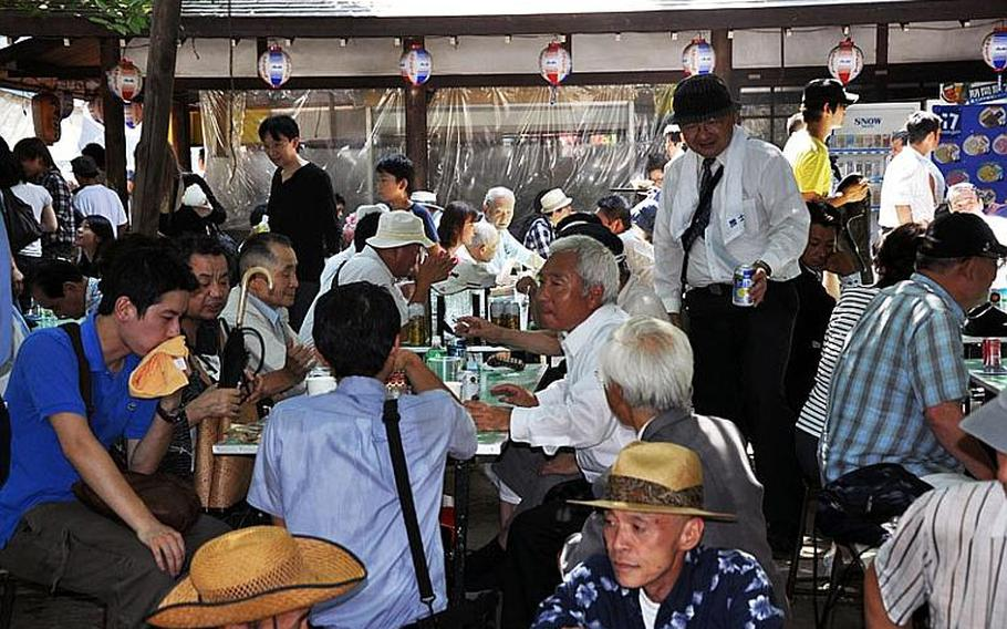 Visitors eat and drink at Yasukuni Shrine to escape the intense heat of the summer day.