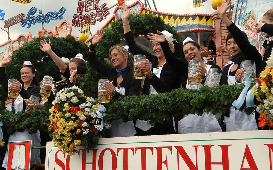 Women riding on the Schottenhamel wagon in the parade of the landlords and breweries wave to spectators on the opening day of Oktoberfest. While they were able to enjoy a beer during their ride, everyone else had to wait for Lord Mayor Christian Ude to tap the first keg at noon.